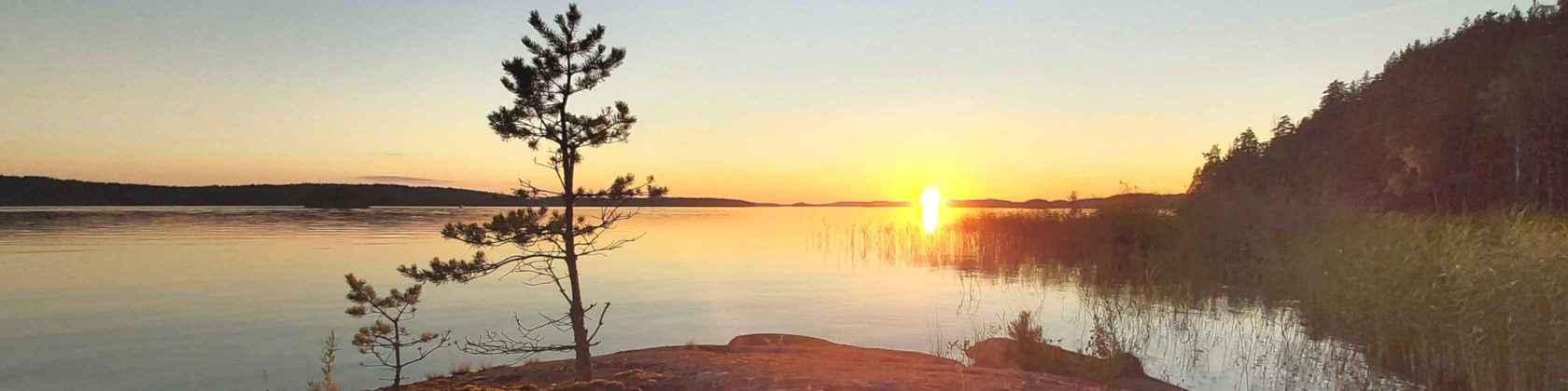 Aurinko laskee tyynen järven selän taakse