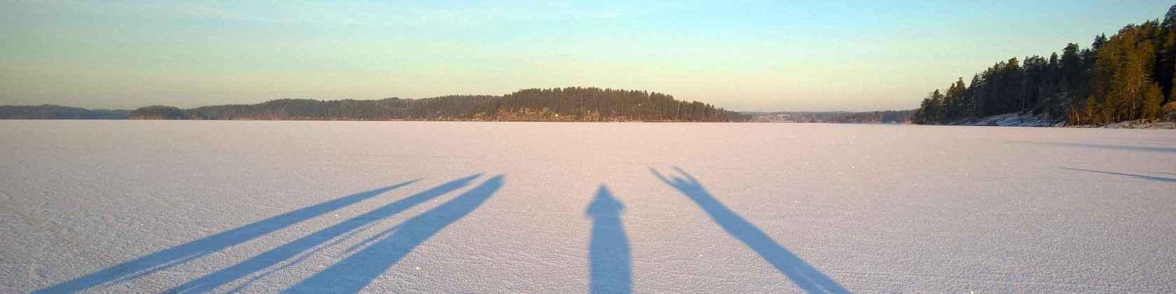 Viisi pitkää ihmisen varjoa valkoisella lumipeitteisellä jäällä