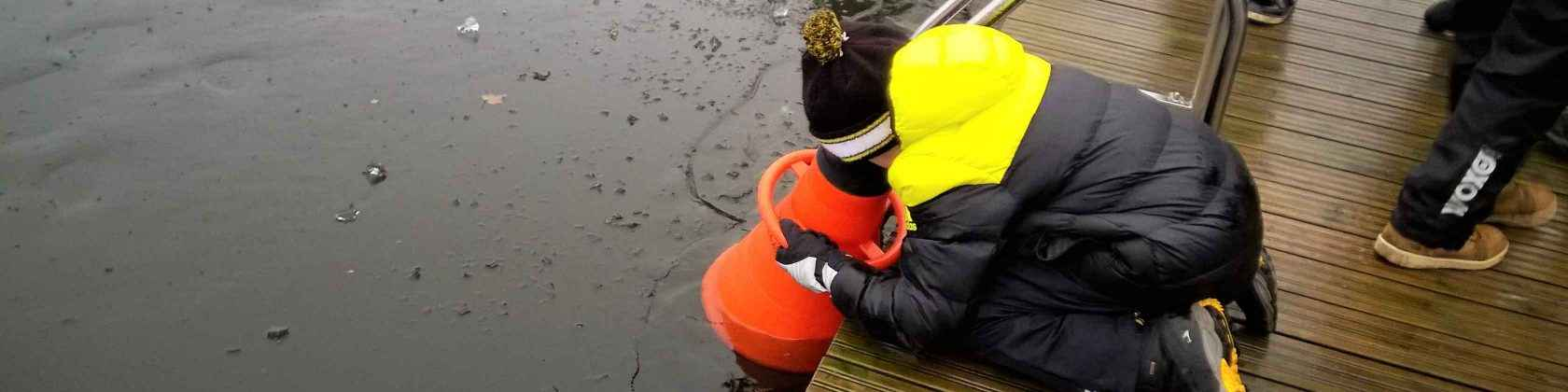 Pikkupoika kurkistaa vesikiikarilla veden pinnan alle