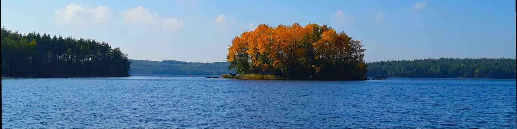 Pieni saari hehkuu ornassina ruskan loisteessa sinisen järven takana