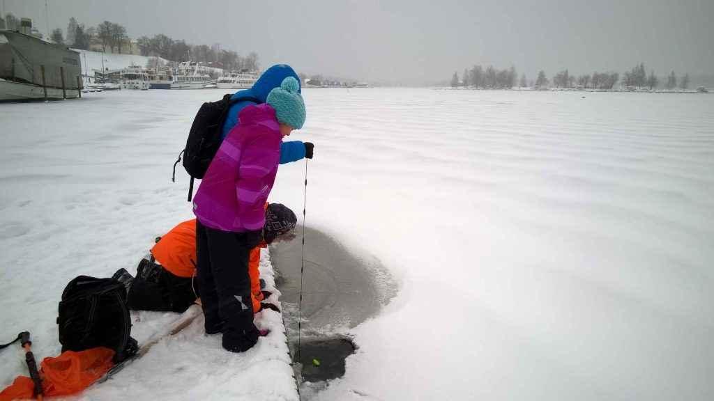 Kolme lasta mittaa talvella avannosta veden lämpötilaa laiturilta