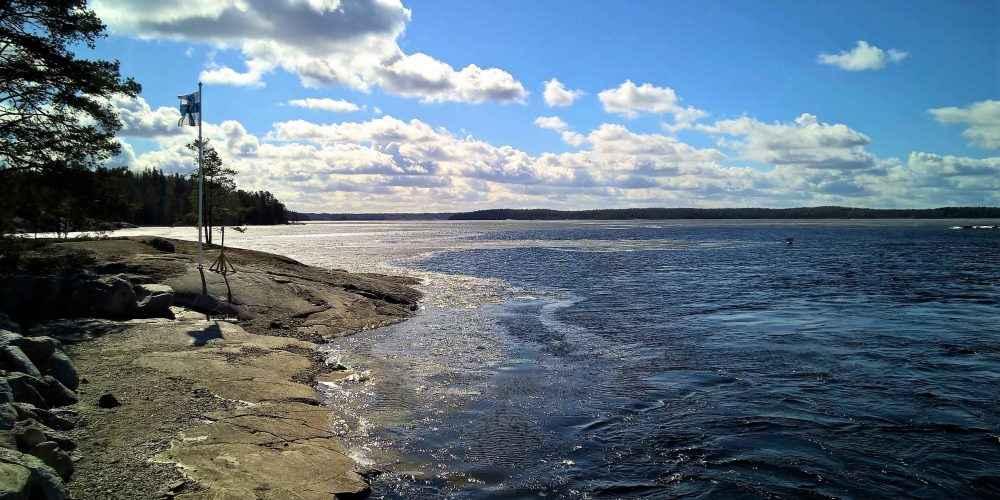 Suomen lippu liehuu tullessa rantakalliolla taustalla sininen järvi ja taivas sekä valkoiset pilvet